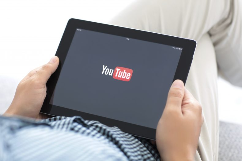 man holding iPad with app YouTube on the screen